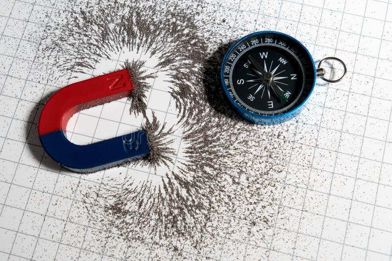 Magnete a ferro di cavallo rosso e blu o fisica magnetica e bussola con il campo magnetico della polvere di ferro sul fondo del g fotografia stock libera da diritti