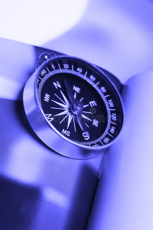 Magnetic compass in blue tone. Magnetic compass on a book royalty free stock image