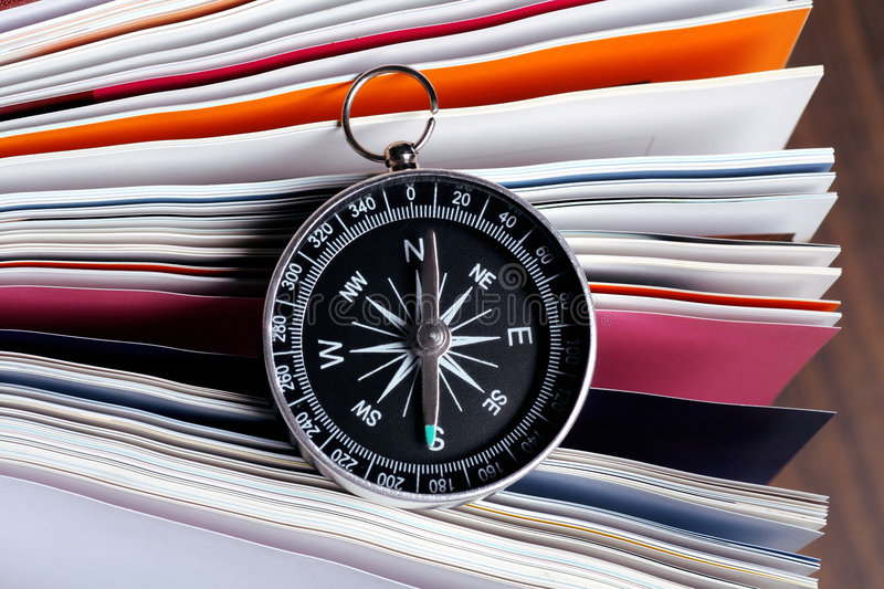 Magnetic compass on a book. With wooden background royalty free stock image