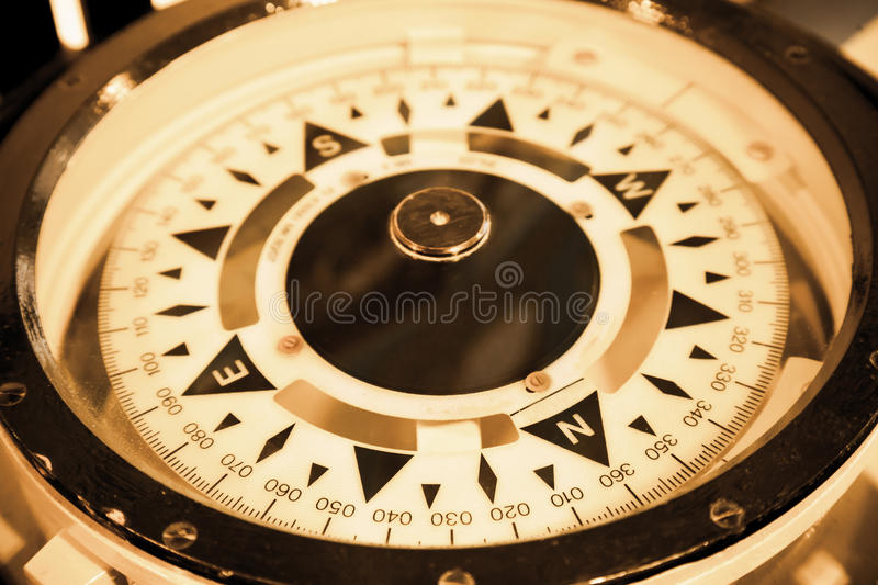 Magnetic compass on the captain bridge. Vintage toned macro photo royalty free stock image