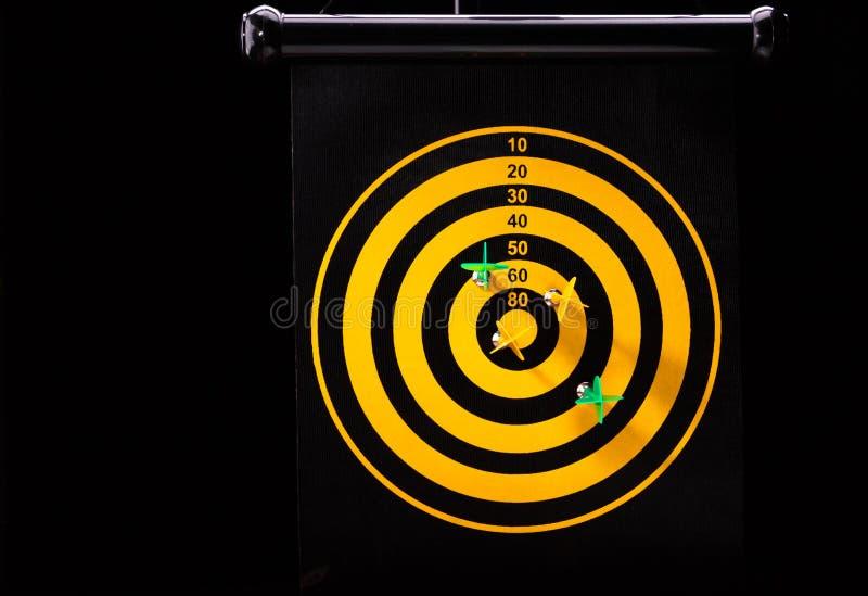 Magnetic dart arrows on yellow dart board. black background. Magnetic green and yellow dart arrows on dart board. black background stock photos