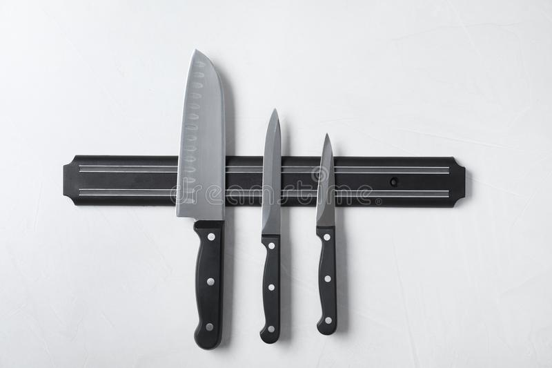 Magnetic holder with set of knives. On grey stone background stock image