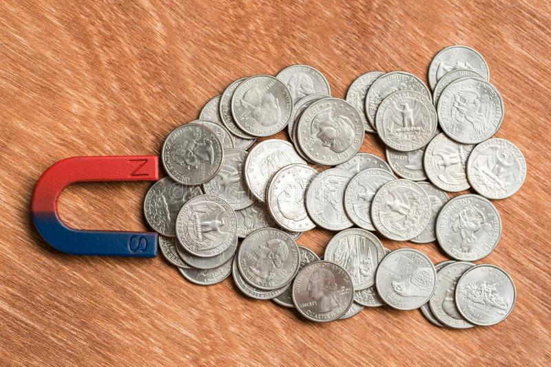 Magnetic pull the coins. On wood background royalty free stock photo