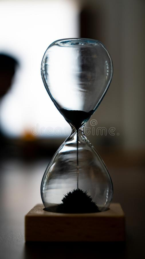 Still Waiting... Magnetic sand hourglass with sand dripping royalty free stock photo