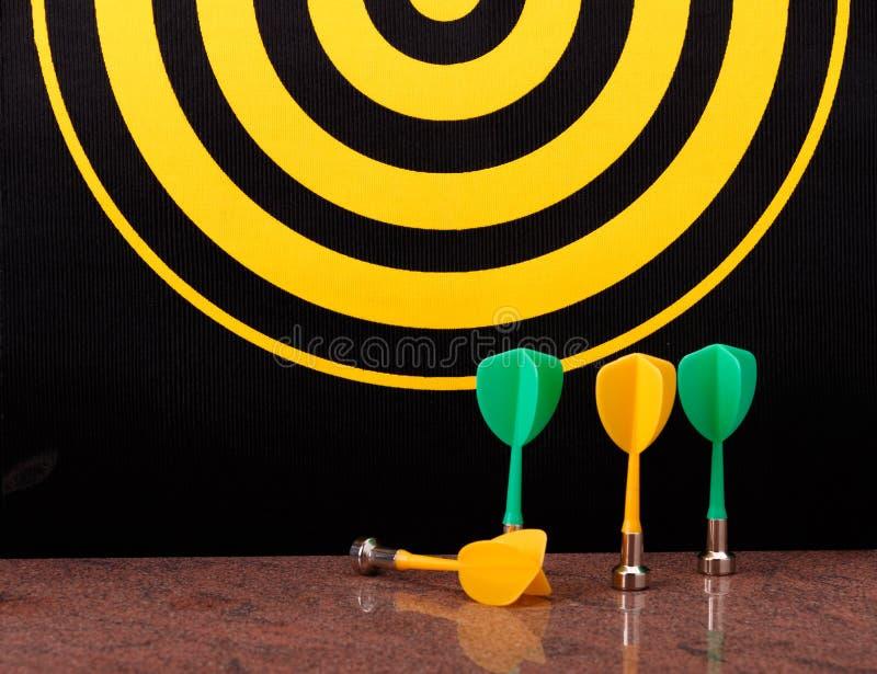 Magnetische Pfeilpfeile auf Granitoberfläche und Dartscheibehintergrund lizenzfreies stockfoto