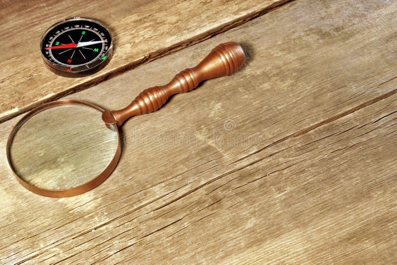 Magnetisk kompass och Retro förstoringsglas på det wood brädet för grunge royaltyfria foton