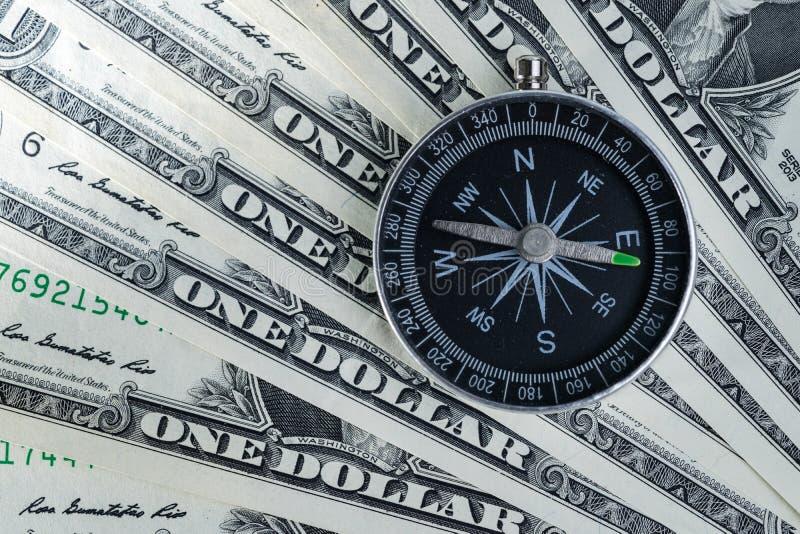 Magnetisk kompass på högen av dollarräkningar som usning som världseconomi arkivbilder