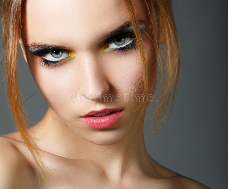 Magnetismo. Carácter. Cara de la belleza roja joven del pelo con maquillaje colorido del ojo imagen de archivo