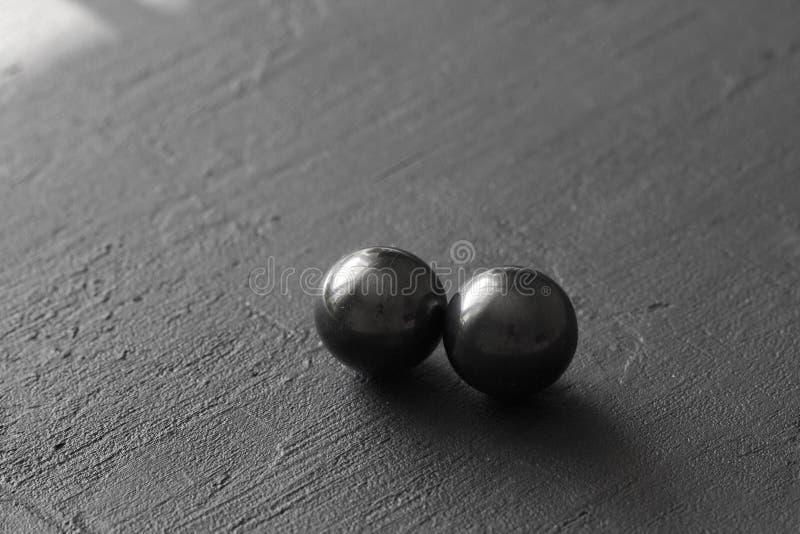 Magnetite di pietra, attrazione, buco nero Le palle naturali di magnetite sono attirate l'un l'altro, su un fondo concreto nero fotografia stock libera da diritti