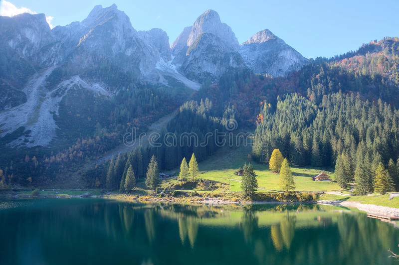 Magnificent autumn scenery of Lake Gosausee with rugged rocky mountain peaks in the background and beautiful reflections on water stock photo