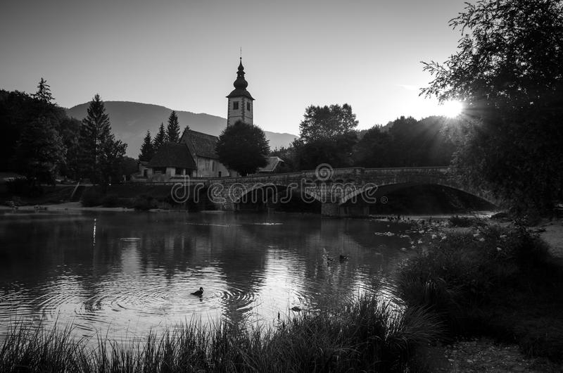 Black and white picture of sunrise over Bohinj lake with Church of St John the Baptist on the lakeside, Bohinj, Slovenia, Europe. Magnificent black and white stock image