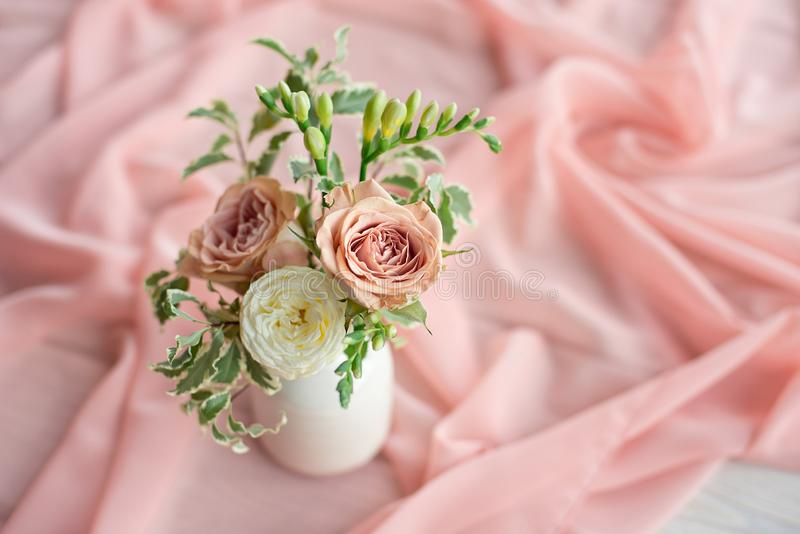 Magnificent bouquet of different flowers is a floral arrangement in a white ceramic vase of a round shape. Table setting stock image