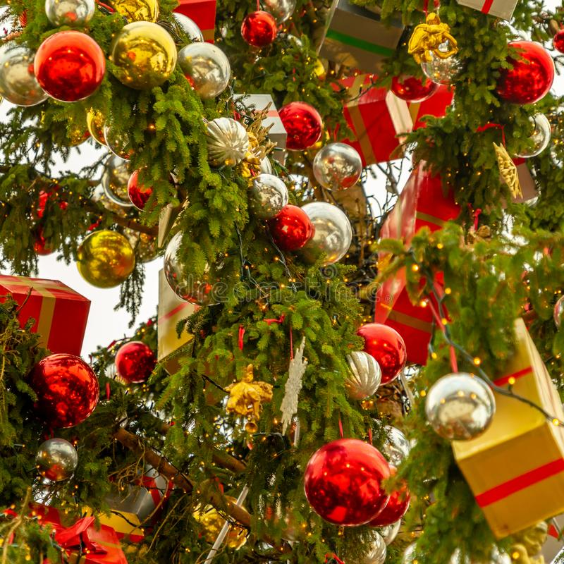 Magnificent Christmas tree decorated with silver and red balls and packages wrapped in wrapping paper, close-up view. stock image