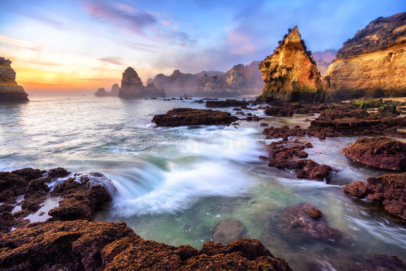 Magnificent coast scenery at sunrise. Magnificent scenery of a coast at sunrise, with warm-colored cliffs, colorful sky and a gentle wave - shot in Lagos stock photography