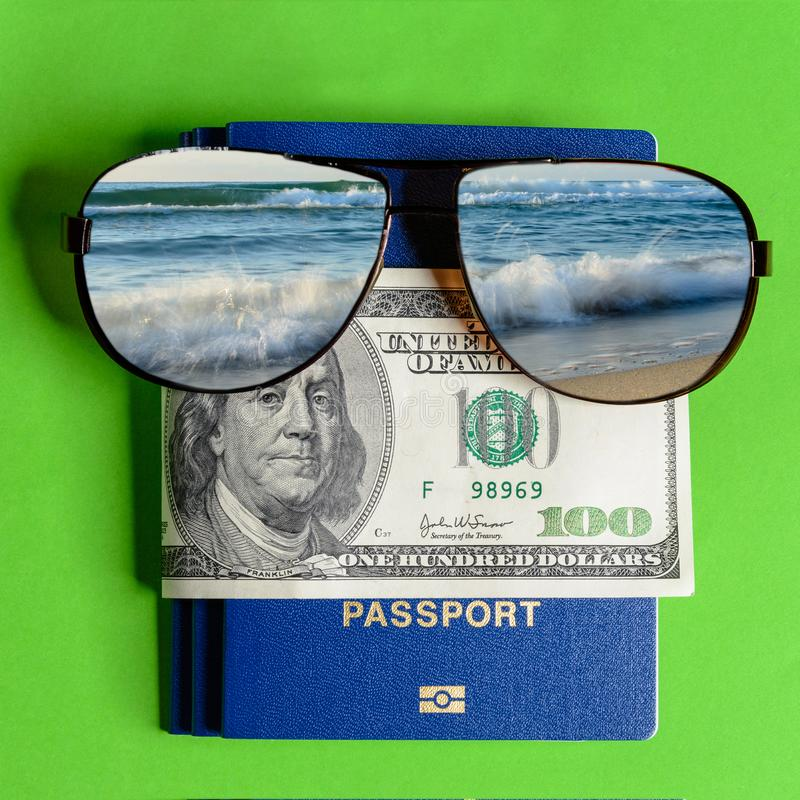 Sunglasses with a reflection of the sea and a passport and one hundred dollars stock photos