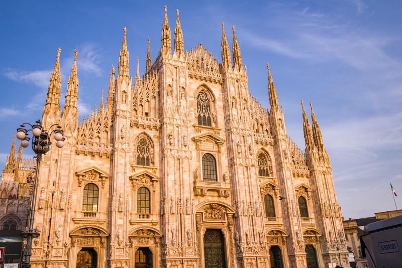 The pink Candoglia marbel glows as sunset approaches the Duomo di Milano. stock photography