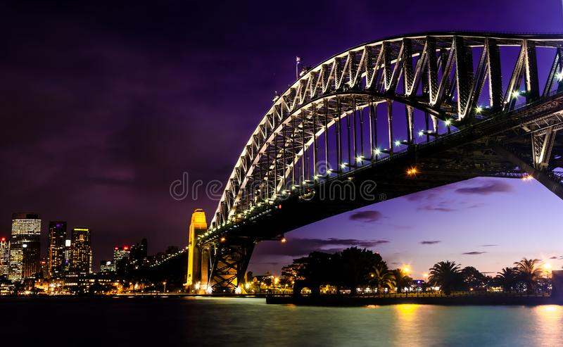 Gorgeous sunset on mighty steel Sydney Harbor bridge crossing the ocean stock images