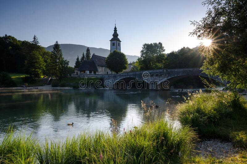Sunrise over Bohinj lake with Church of St John the Baptist on the lakeside, Bohinj, Slovenia, Europe. Magnificent morning view from a bank of Bohinj lake with stock photo
