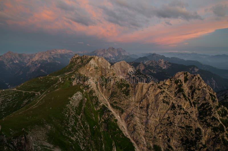 Illuminated reddish clouds over Mangart Pass and road, Julian Alps, Triglav national park, Slovenia, Europe stock images
