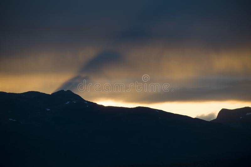 Magnificent silhouette view of the Norwegian mountains in sunset sky. A magnificent silhouette view of the Norwegian mountains in sunset sky stock images