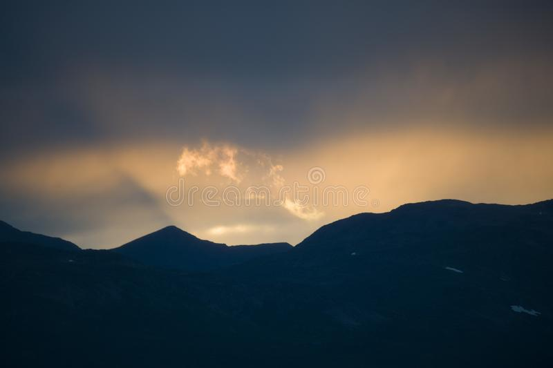 Magnificent silhouette view of the Norwegian mountains in sunset sky. A magnificent silhouette view of the Norwegian mountains in sunset sky stock photography
