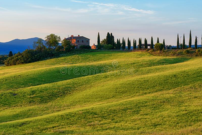 Magnificent spring landscape at sunrise.Beautiful view of typical tuscan farm house, green wave hills. Magnificent spring landscape at sunrise.Beautiful view of stock image