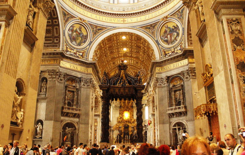 Magnificent St. Peter`s Basilica interior Vatican. View of the rich St. Peter`s Basilica interior,nave full of visitors and High Altar is surmounted by Bernini's royalty free stock photography
