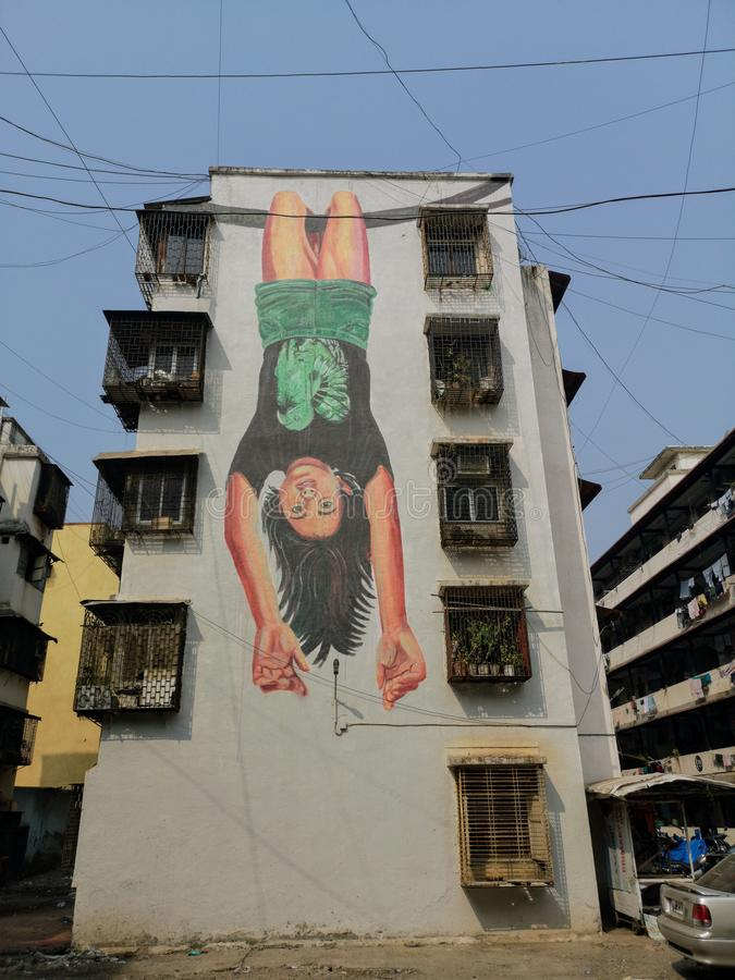Magnificent street art graffiti of little girl hanging upside down in Mahim east Mumbai. stock photography