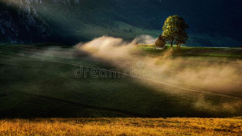 Magnificent sunrise in the Transylvania region with mist and sun ray. Magnificent sunrise in the Carpathian mountains with mist and shepherd house stock photo