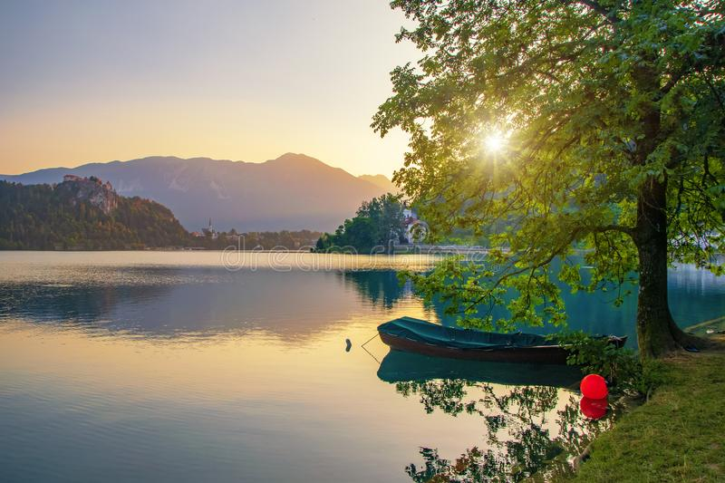 Magnificent sunrise over Lake Bled, Slovenia at summer morning. Magnificent sunrise over Lake Bled, Slovenia. Boat moored near lone tree. Sun shines through the royalty free stock photography