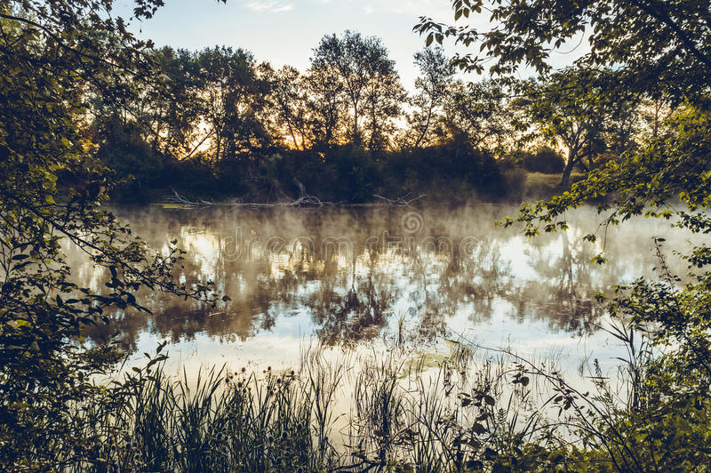 A magnificent sunrise on a river. With a mist over the water royalty free stock photos