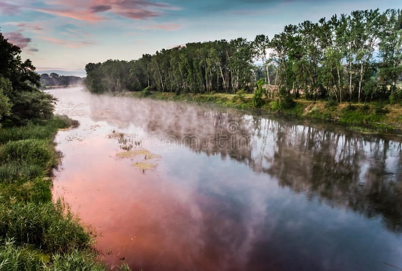 Magnificent sunrise on the river. In the summer with fog over the water stock photography