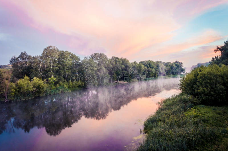 Magnificent sunrise on the river. In the summer with fog over the water stock image