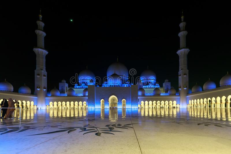 Magnificent view of the inner area of The Sheikh Zayed Grand Mosque, beautifully illuminated with blue light in the evening royalty free stock photo