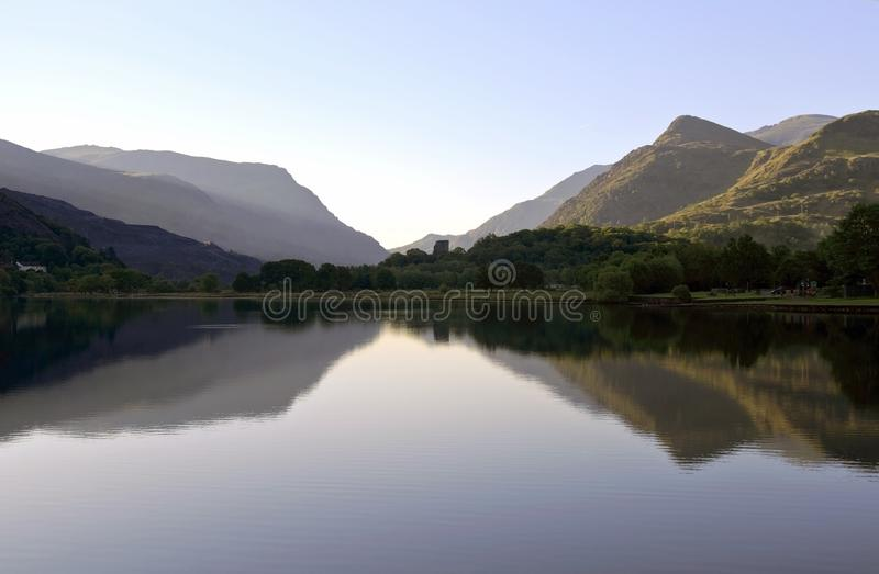 Beautiful Welsh Mountains reflected in a still waters of lake Llyn Padarn, Llan Beris Wales. Magnificent Welsh Mountains and trees reflected in a still waters of royalty free stock photography