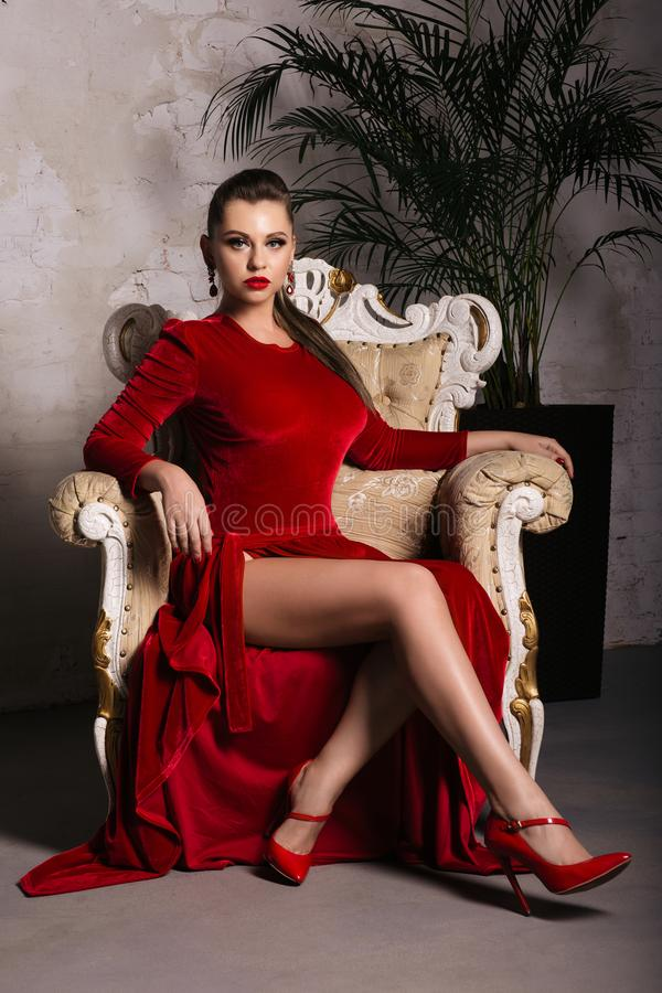 Magnificent young woman in luxurious red dress and precious jewelery is sitting in a chair in a luxury apartment. Classic vintage stock photos