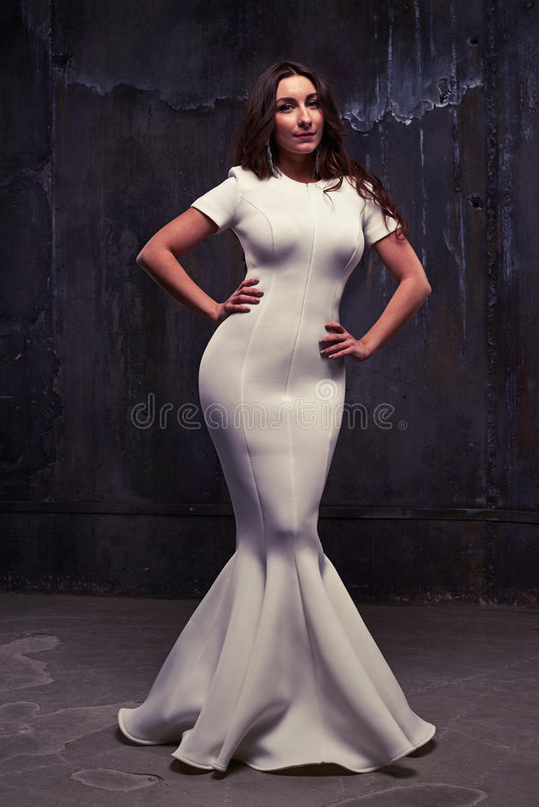 Magnificent young woman in a white fishtail maxi dress over black worn background stock photo
