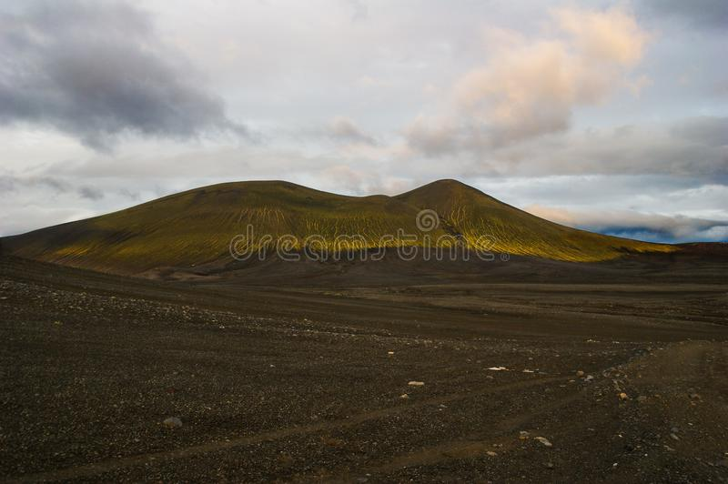 Magnificent volcanic scenery on the road to Landmannalaugar, Iceland. Black volcanic ash covered by green mosses royalty free stock photography