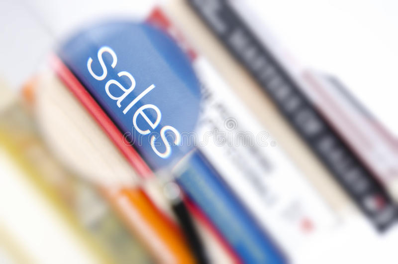 Magnified Sales. Sales word magnified from the spine cover of a blue book in a stack stock image