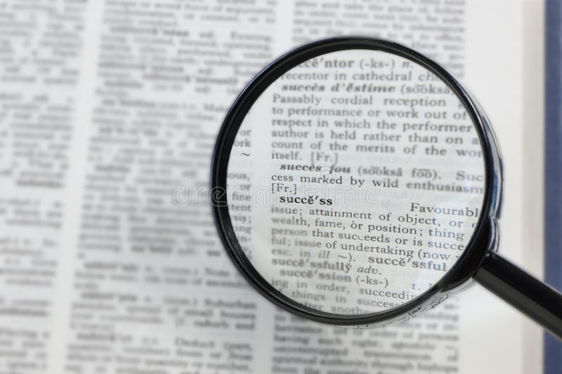 Magnified Success. The word success in a dictionary, seen through a magnifying glass stock images