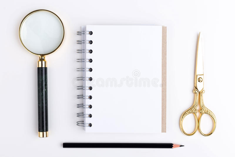 Magnifier, σημειωματάριο και ψαλίδι στοκ φωτογραφίες