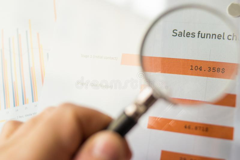 Magnifier on a coloured funnel chart printed on a white sheet of paper during a business meeting. Male hand pointing at a coloured funnel chart printed on a royalty free stock photo