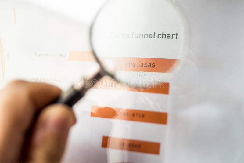 Magnifier on a coloured funnel chart printed on a white sheet of paper during a business meeting. Male hand pointing at a coloured funnel chart printed on a stock images