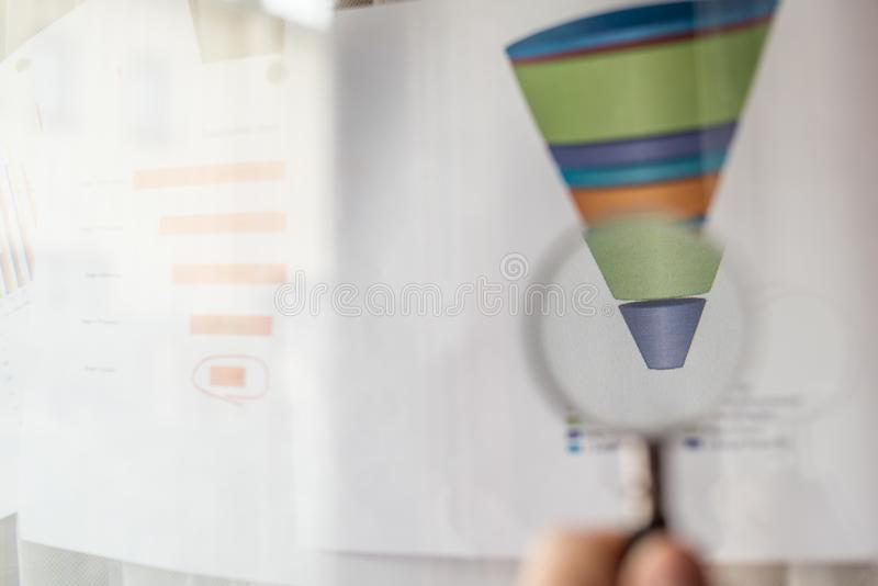 Magnifier on a coloured funnel chart printed on a white sheet of paper during a business meeting. Male hand pointing at a coloured funnel chart printed on a royalty free stock photos