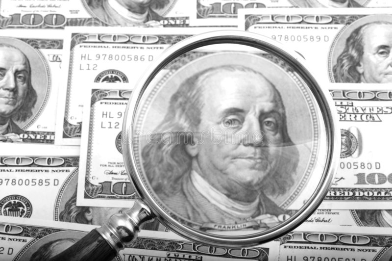 Magnifier com close up do dinheiro imagens de stock
