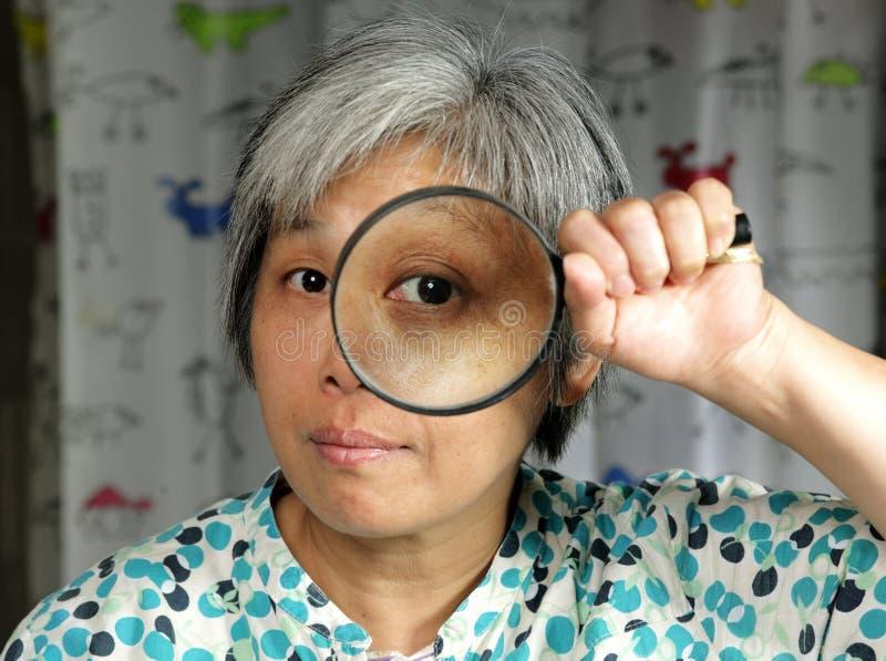 magnifier da terra arrendada da mulher do middleage fotografia de stock royalty free