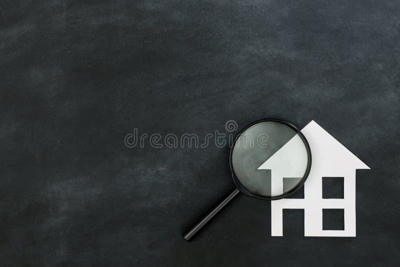 Magnifier die huis zoeken dat op bord wordt geïsoleerd royalty-vrije stock afbeelding