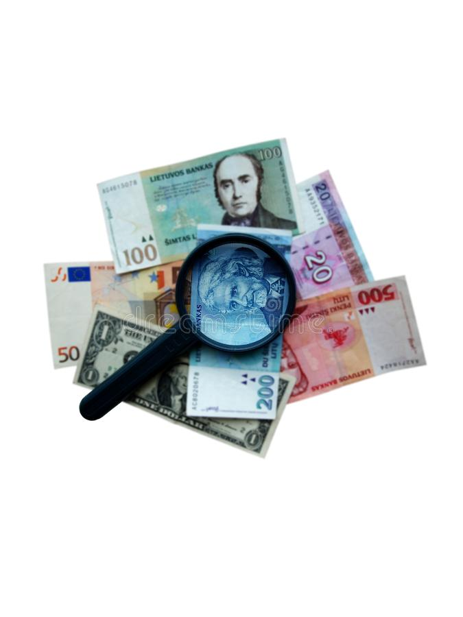 Magnifier on different banknotes stock images