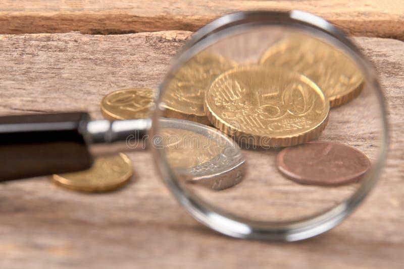 Magnifier e moedas foto de stock