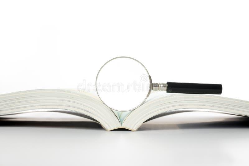 Magnifier en boek stock afbeelding